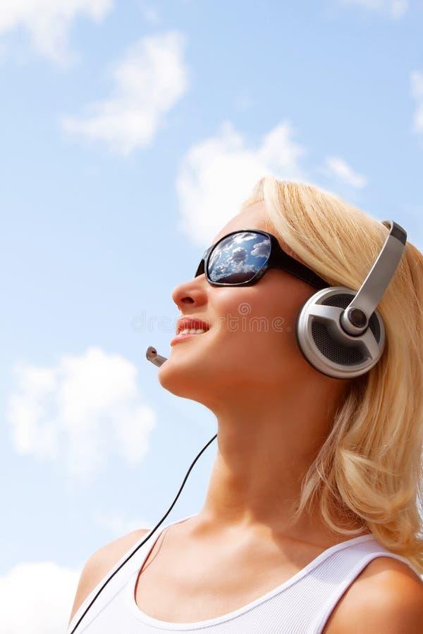 Retrato de la mujer joven atractiva feliz con los auriculares foto de archivo