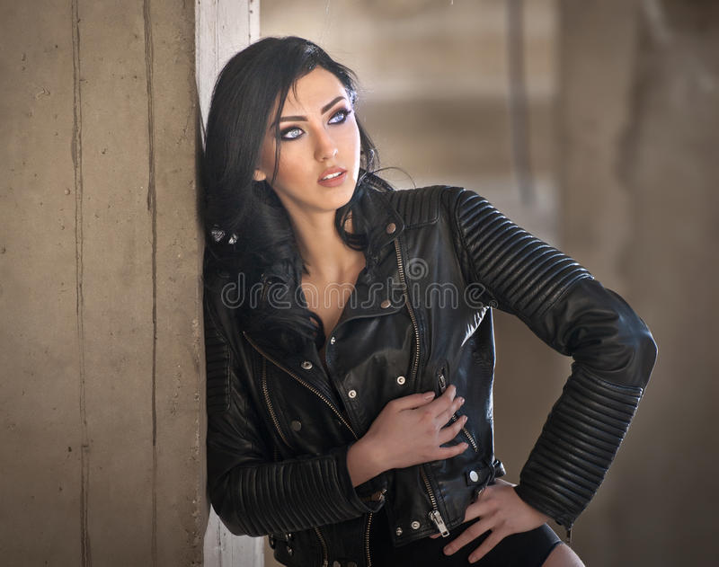 Retrato de la mujer joven atractiva hermosa con el equipo negro, chaqueta de cuero sobre la ropa interior, en fondo urbano foto de archivo