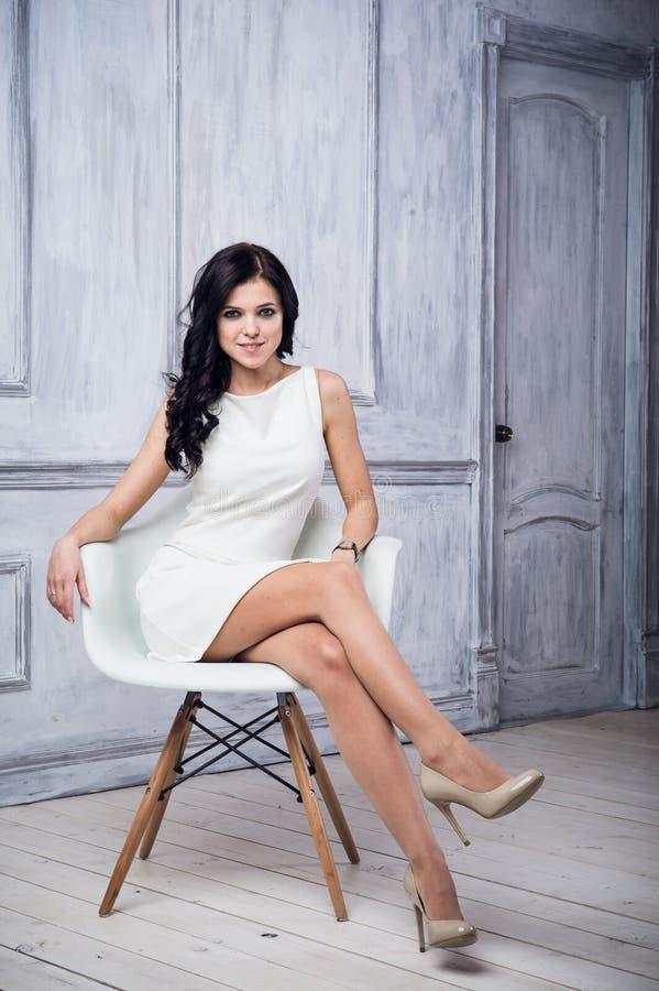 Retrato de la mujer joven atractiva que se sienta en una silla Vestido blanco elegante Piso blanco y pared blanca en el fondo imagenes de archivo