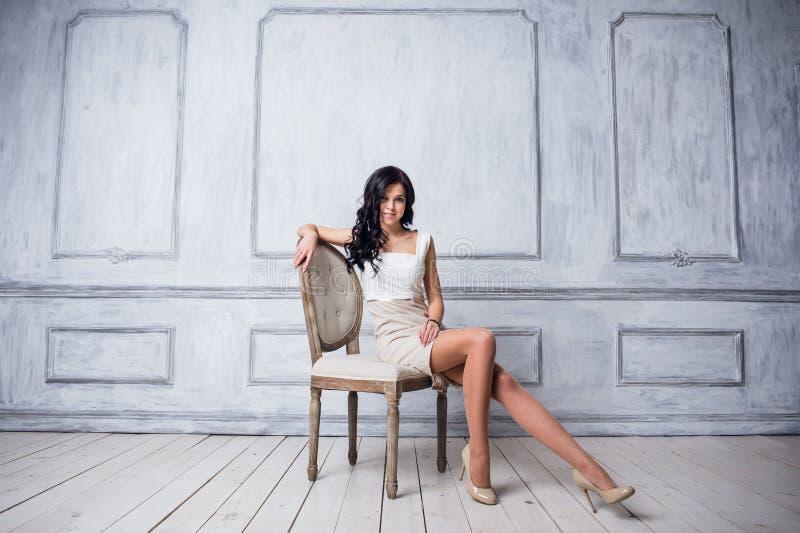 Retrato de la mujer joven atractiva que se sienta en una silla Vestido blanco elegante Piso blanco y pared blanca en el fondo imagen de archivo