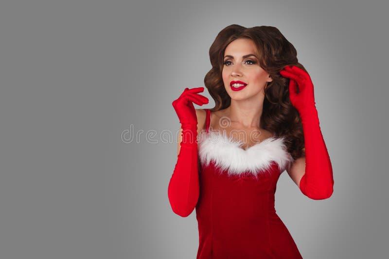 Retrato de la mujer joven, atractiva y hermosa en vestido de la Navidad Fondo gris Concepto de la Navidad, de Navidad, de Navidad fotografía de archivo