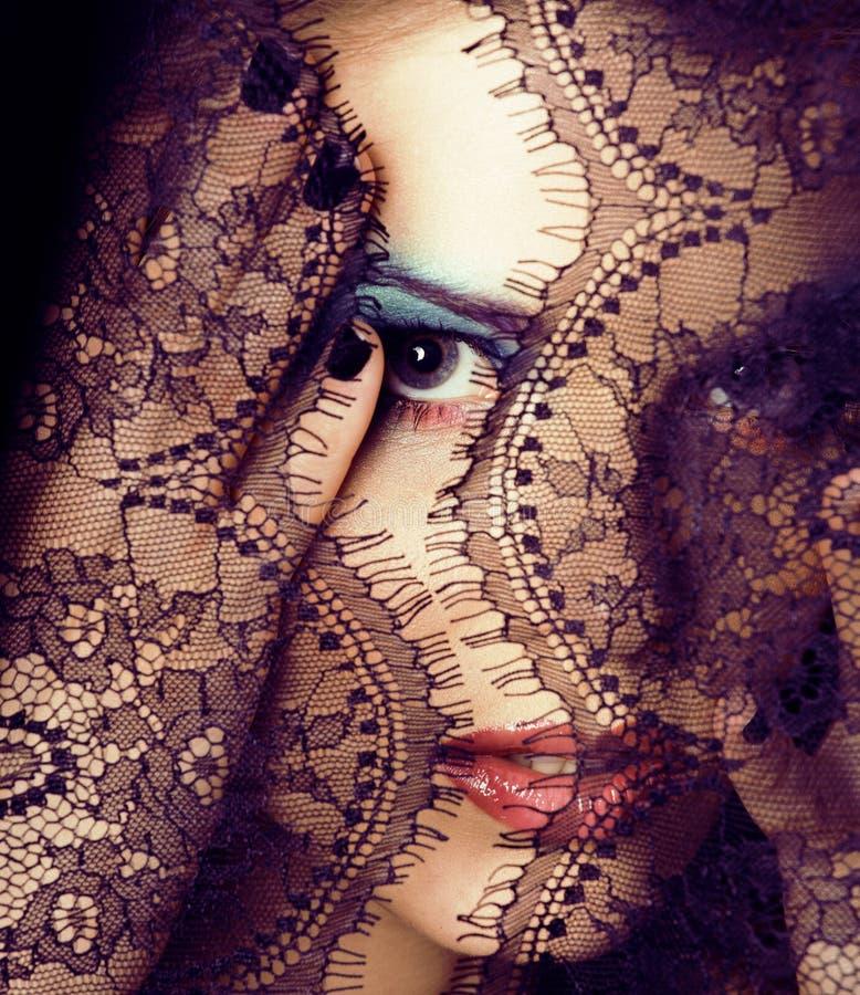 Retrato de la mujer joven de la belleza a través del cordón imágenes de archivo libres de regalías