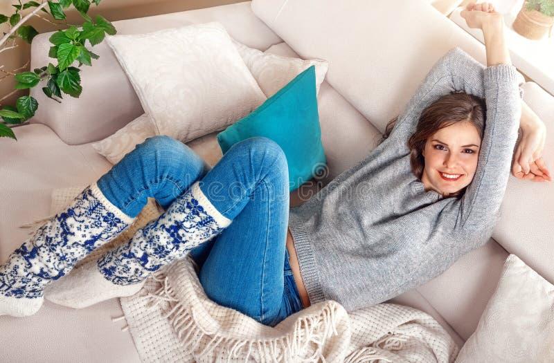 Retrato de la mujer joven bonita positiva que se relaja en el sofá fotografía de archivo