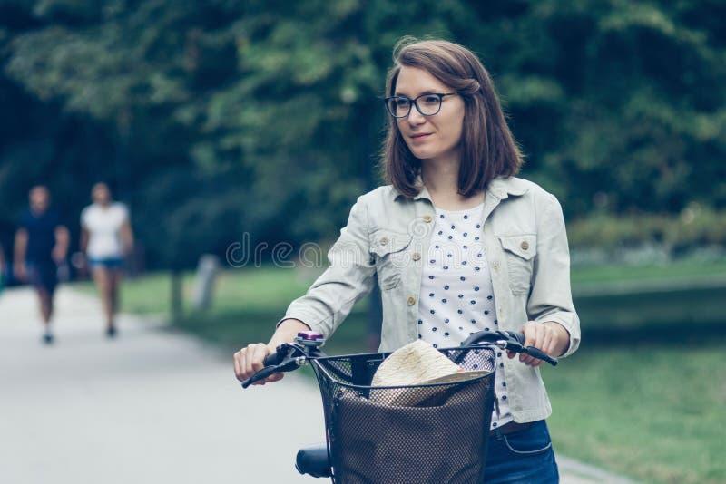 Retrato de la mujer joven con la bicicleta en parque imágenes de archivo libres de regalías