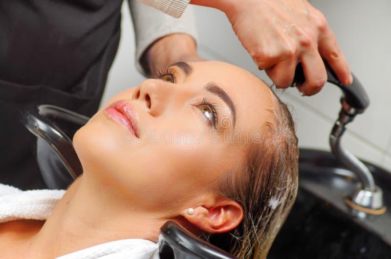 Retrato de la mujer joven con la cabeza que se lava del peluquero en el salón de pelo, la belleza y el concepto de la gente foto de archivo