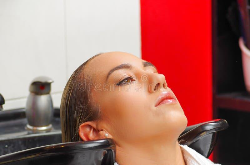 Retrato de la mujer joven con la cabeza que se lava del peluquero en el salón de pelo, la belleza y el concepto de la gente imagen de archivo