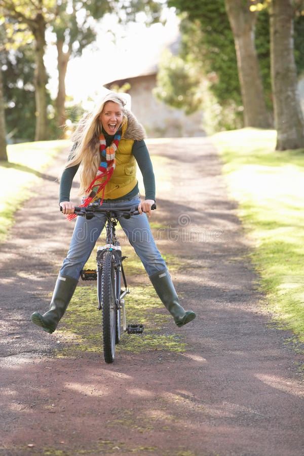 Retrato de la mujer joven con el ciclo en parque del otoño foto de archivo