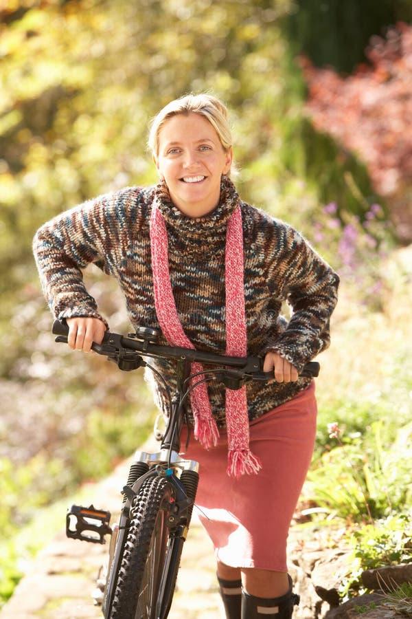 Retrato de la mujer joven con el ciclo en parque del otoño imágenes de archivo libres de regalías