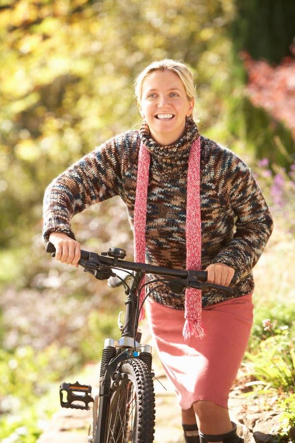 Retrato de la mujer joven con el ciclo en parque del otoño imagen de archivo