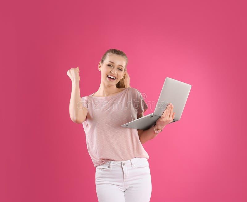 Retrato de la mujer joven con el ordenador portátil en rosa foto de archivo libre de regalías