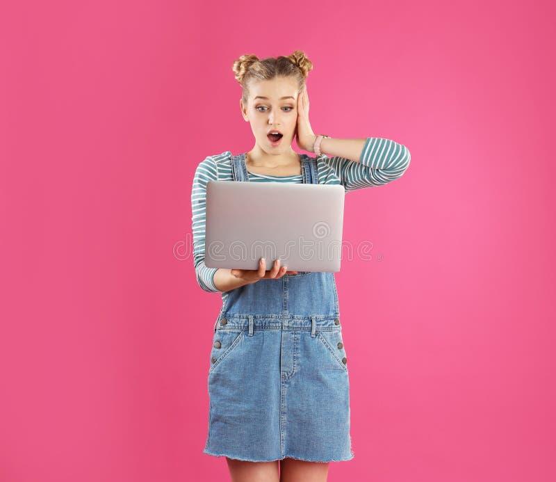 Retrato de la mujer joven con el ordenador portátil en rosa imagenes de archivo