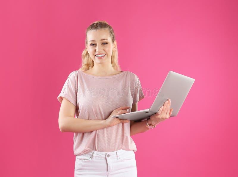 Retrato de la mujer joven con el ordenador portátil en rosa fotos de archivo