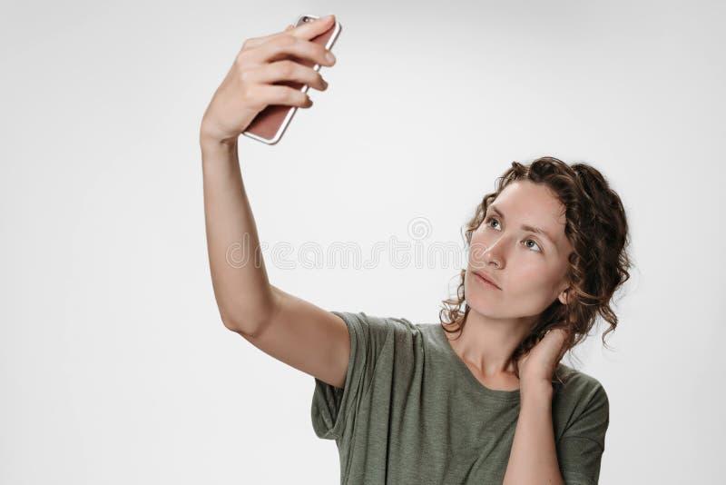 Retrato de la mujer joven con el pelo rizado que tiene v?deo-llamada que sostiene el tel?fono elegante fotos de archivo