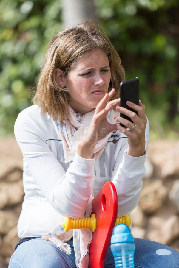 Retrato de la mujer joven con el teléfono celular en patio fotografía de archivo libre de regalías