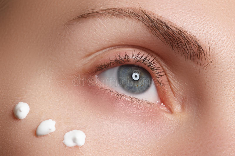 Retrato de la mujer joven con la cara limpia fresca con los puntos de la crema hidratante debajo del ojo foto de archivo