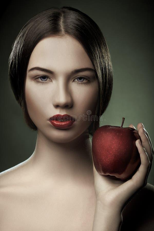 Retrato de la mujer joven con la manzana imagenes de archivo