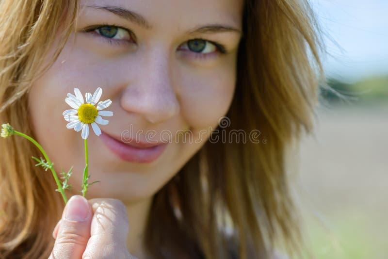 Retrato de la mujer joven con la manzanilla foto de archivo