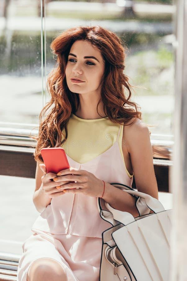 retrato de la mujer joven con sentarse del smartphone fotos de archivo