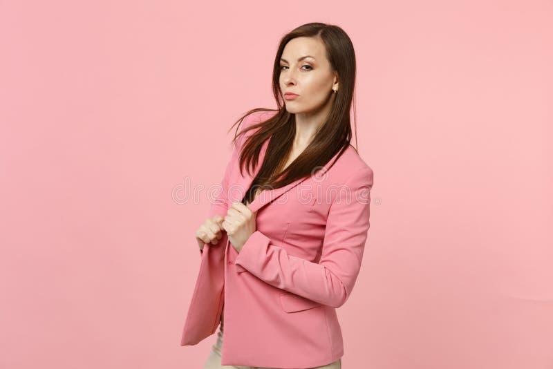 Retrato de la mujer joven confiada imponente que lleva, sosteniendo la chaqueta que mira la cámara aislada en la pared rosada en  foto de archivo libre de regalías