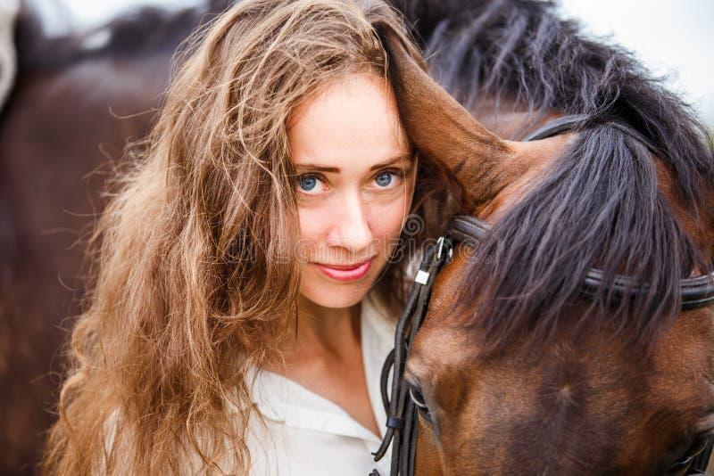 Retrato de la mujer joven del jinete con su caballo de bahía fotos de archivo libres de regalías