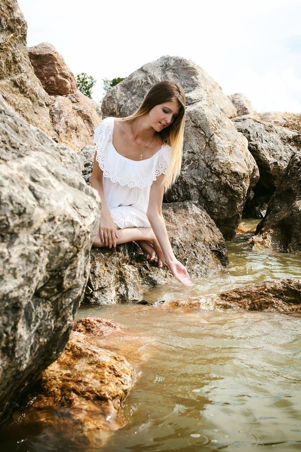 Retrato de la mujer joven delgada en piedras cerca del mar imagen de archivo
