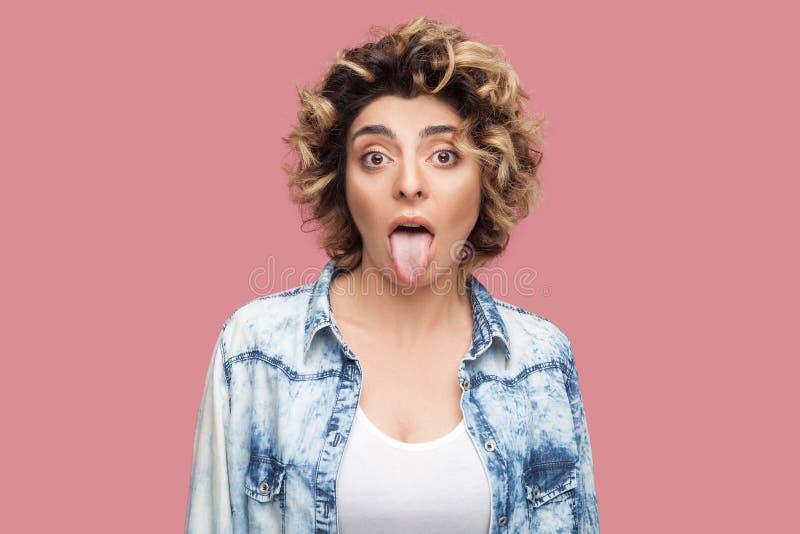 Retrato de la mujer joven divertida loca o chocada con el peinado rizado en la situaci?n azul casual de la camisa, lengua hacia f imagenes de archivo