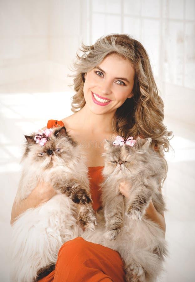 Retrato de la mujer joven elegante que sostiene dos gatos persas adorables imagen de archivo