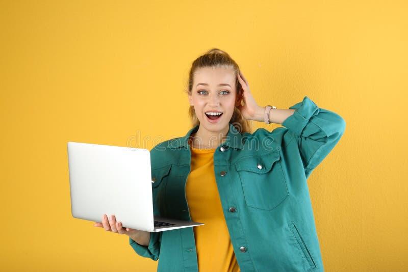 Retrato de la mujer joven emocional con el ordenador portátil fotografía de archivo