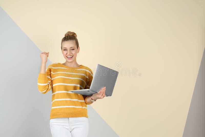 Retrato de la mujer joven emocional con el ordenador portátil en fondo del color fotos de archivo libres de regalías