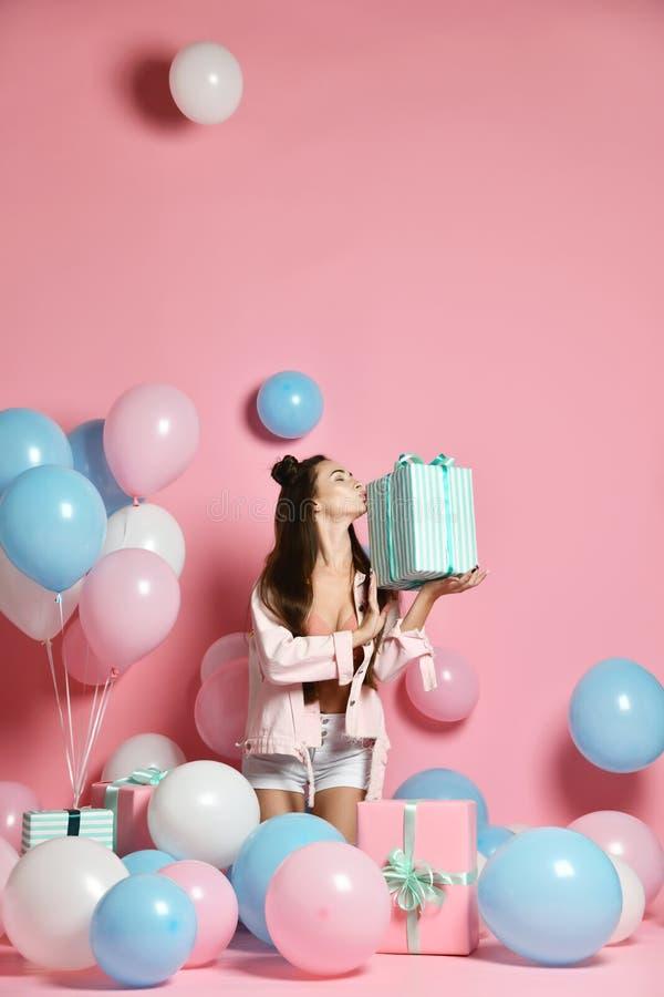 Retrato de la mujer joven en caja de regalo de la tenencia de la fiesta de cumpleaños con el presente del regalo en fondo rosado  foto de archivo