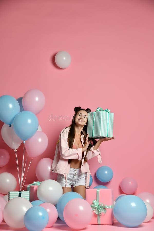 Retrato de la mujer joven en caja de regalo de la tenencia de la fiesta de cumpleaños con el presente del regalo en fondo rosado  fotos de archivo libres de regalías