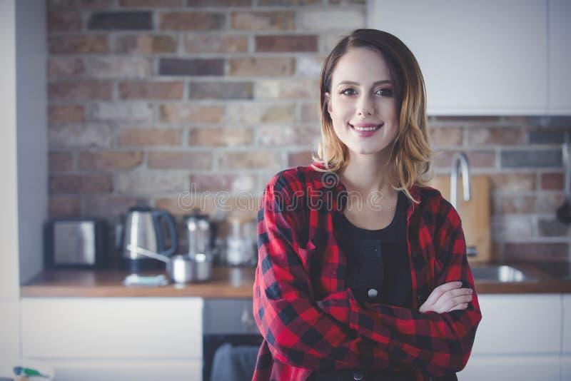 Retrato de la mujer joven en camisa roja en la cocina imágenes de archivo libres de regalías