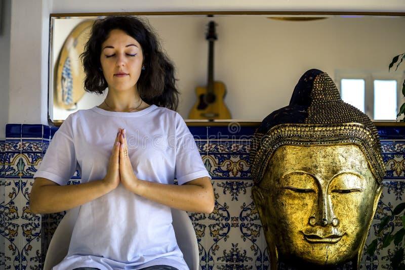 Retrato de la mujer joven en la camiseta blanca y con el pelo corto que se sienta en actitud de la meditación fotos de archivo