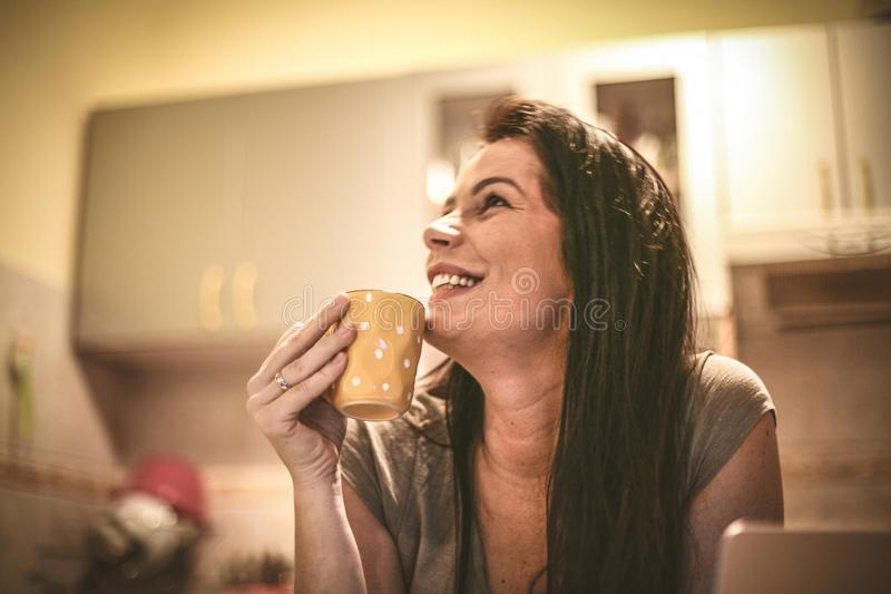 Retrato de la mujer joven en casa que bebe el café imagen de archivo libre de regalías