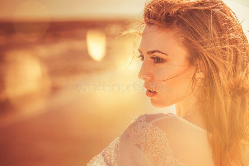 retrato de la mujer joven en la costa de la puesta del sol fotografía de archivo