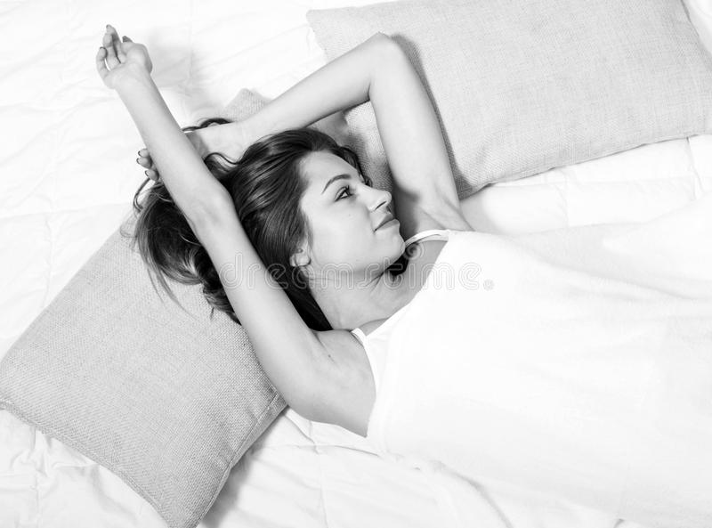 Retrato de la mujer joven en dormitorio en de la cama la relajación solamente blanco y negro foto de archivo libre de regalías