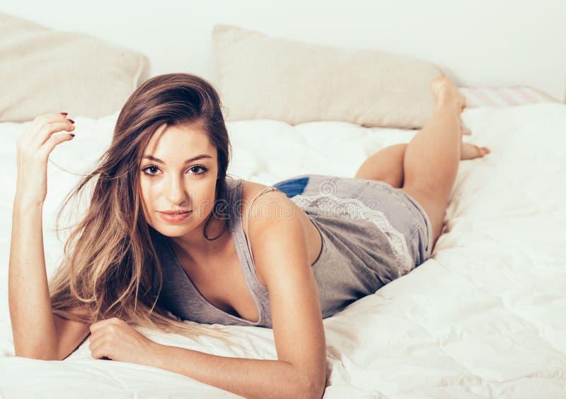 Retrato de la mujer joven en dormitorio en la cama solamente que se relaja mirando la cámara fotos de archivo