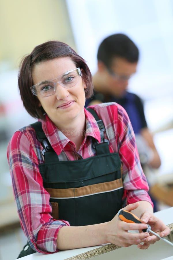Retrato de la mujer joven en el entrenamiento de la carpintería imágenes de archivo libres de regalías