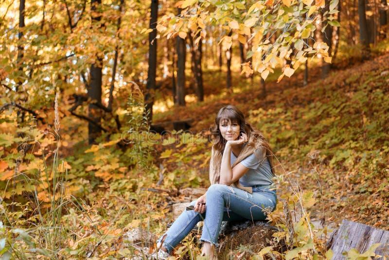 Retrato de la mujer joven en el parque del otoño que se sienta en un registro de madera Árboles con follaje amarillo en el fondo, foto de archivo libre de regalías