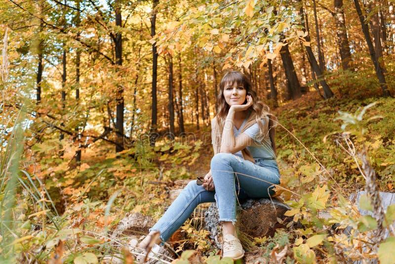 Retrato de la mujer joven en el parque del otoño que se sienta en un registro de madera Árboles con follaje amarillo en el fondo, imagen de archivo