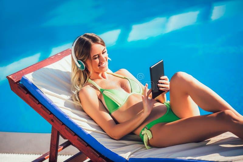 Retrato de la mujer joven en el sol tropical cerca de la piscina fotos de archivo