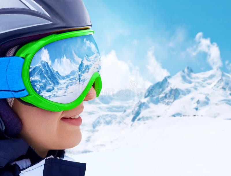 Retrato de la mujer joven en la estación de esquí en el fondo de montañas y del cielo azul Una cordillera reflejada en la máscara foto de archivo libre de regalías