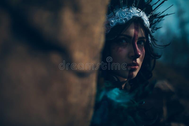 Retrato de la mujer joven en la imagen de una hada y una situación de la bruja al lado de la roca foto de archivo