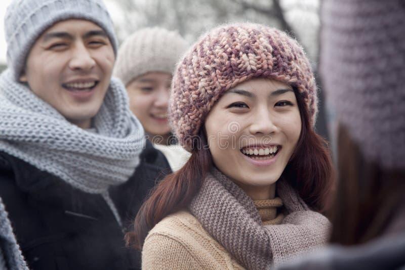 Retrato de la mujer joven en invierno con los amigos imágenes de archivo libres de regalías