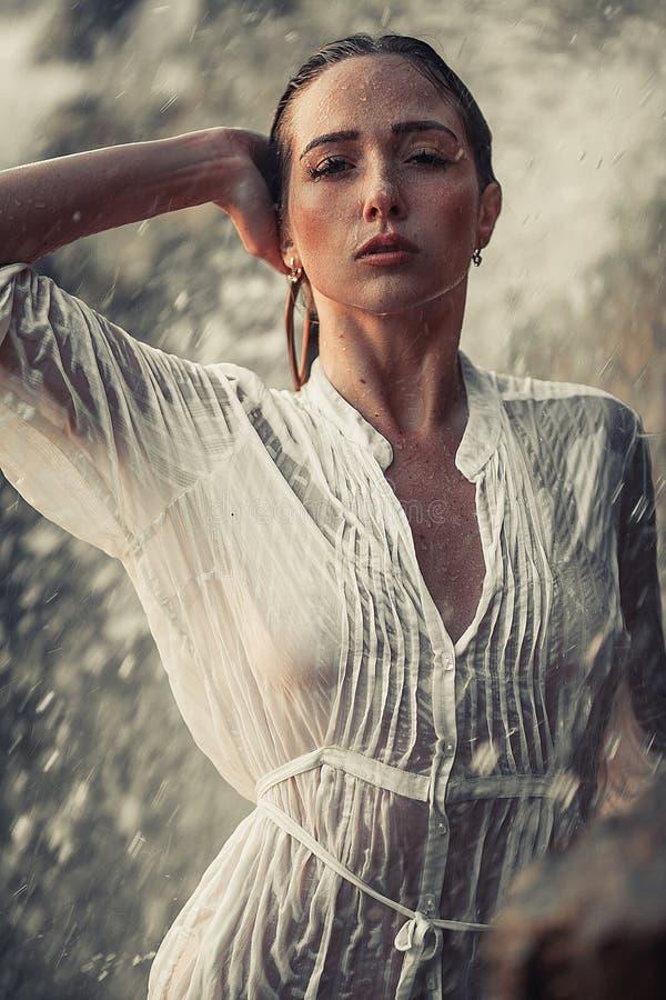 Retrato de la mujer joven en la camisa mojada blanca cerca de la cascada imagenes de archivo