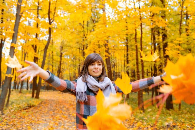 Retrato de la mujer joven en mujer morena del bosque de la caída en parque del otoño con la capa y la bufanda de moda de la tela  imagen de archivo libre de regalías