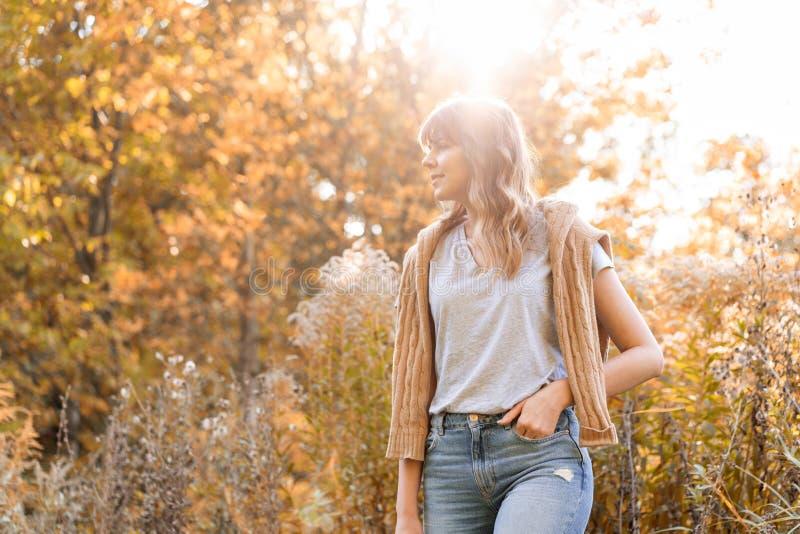 Retrato de la mujer joven en parque del otoño Árboles con el follaje amarillo en el fondo, luz hermosa de la puesta del sol calie foto de archivo libre de regalías