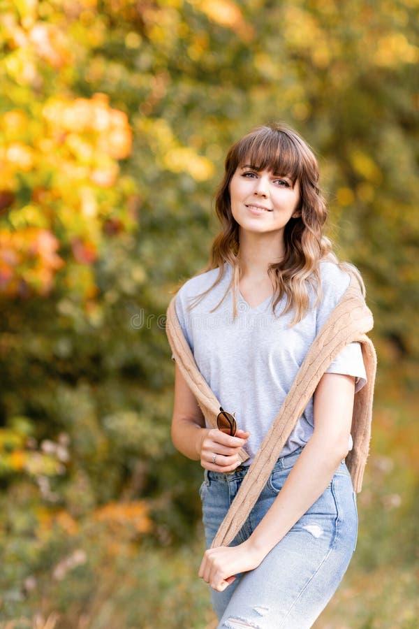 Retrato de la mujer joven en parque del otoño Árboles con el follaje amarillo en el fondo, luz hermosa de la puesta del sol calie imagen de archivo libre de regalías