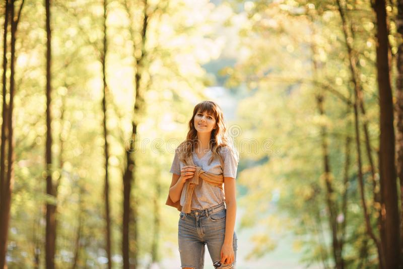 Retrato de la mujer joven en parque del otoño Árboles con el follaje amarillo en el fondo, luz hermosa de la puesta del sol calie imagen de archivo