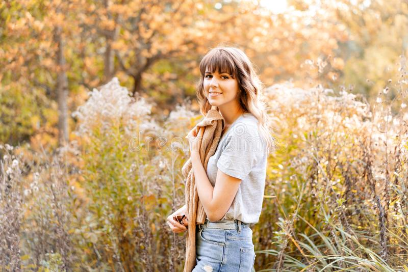 Retrato de la mujer joven en parque del otoño Árboles con el follaje amarillo en el fondo, luz hermosa de la puesta del sol calie fotos de archivo